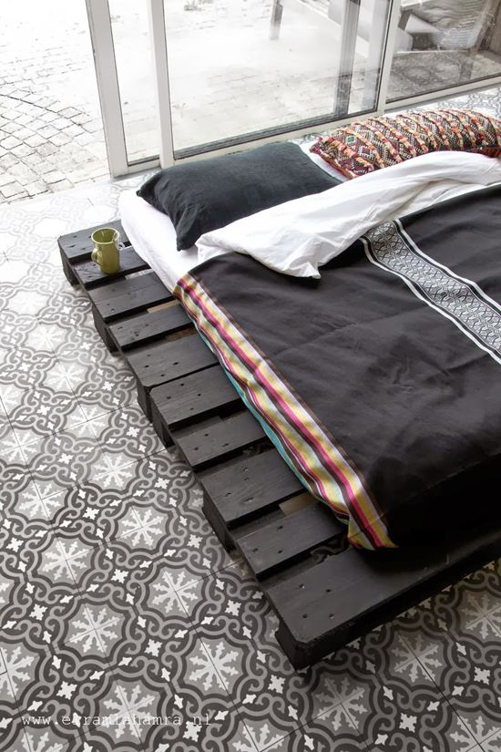 Sommier en palettes noirs sur sol en carreaux de ciment pour une ambiance zen et reposante - recup - economique