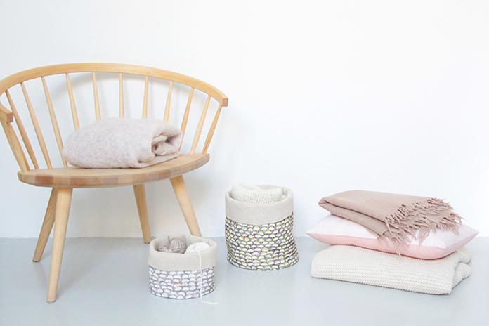 paniers de rangements, linge de lit sur chaise en bois clair
