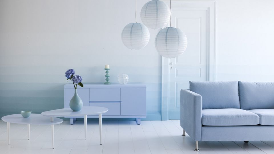 Salon bleu, canapé bleu clair, trois suspensions boules japonaises, deux tables basses aux lignes vintage, buffet bas bleu clair et dégradé de bleu tie and dye sur les murs