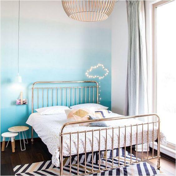 Chambre d'ado avec un lit en fer forgé de couleur cuivre, mur tie and dye bleu, suspension en guise de lampe de chevet, nuage en guirlande lumineuse au mur, et grande suspension au milieu de la pièce