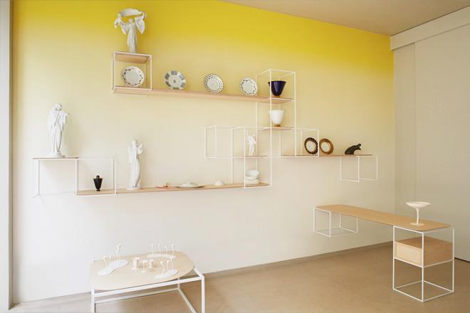 Mur jaune tie and dye dans un intérieur très contemporain, étagères de rangement très fines et graphiques