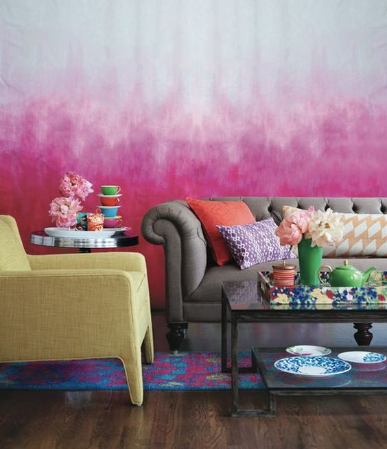 Salon mix and match au style hippie, canapé chesterfield gris, mur tie and dye rose