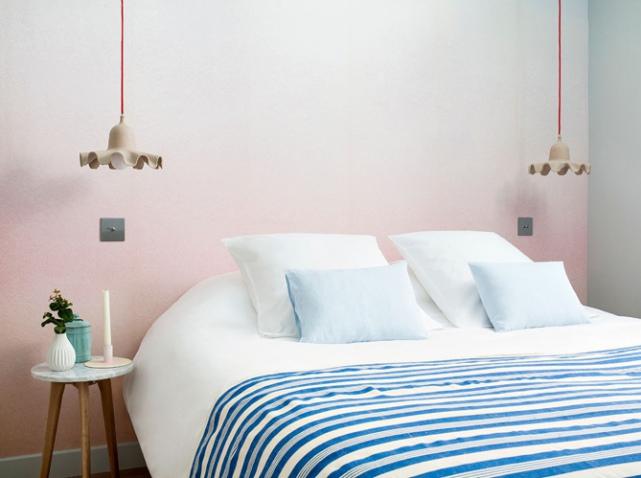 mur tie and dye rose dans une chambre à coucher. Lit blanc avec un plaid rayé bleu et blanc, deux suspension cartonnées de part et d'autre du lit. Un tabouret bois et marbre en guise de chevet.
