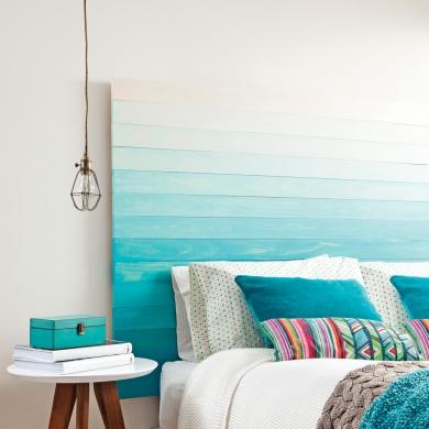 tête de lit en planches de bois teintes façon tie and dye bleu, coussins colorés bleu et bariolés, suspension baladeuse