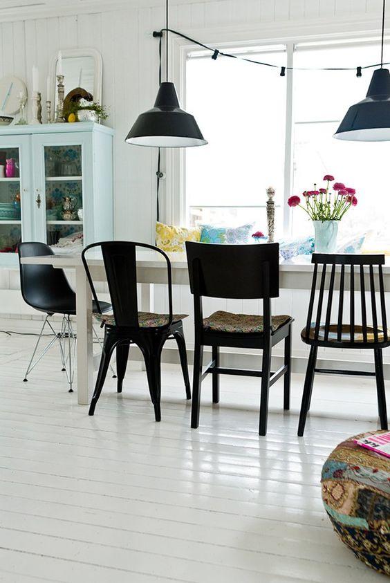 Des chaises dépareillées de couleur noir dans la salle à manger. Style industriel et guirlande guinguette sont à l'honneur