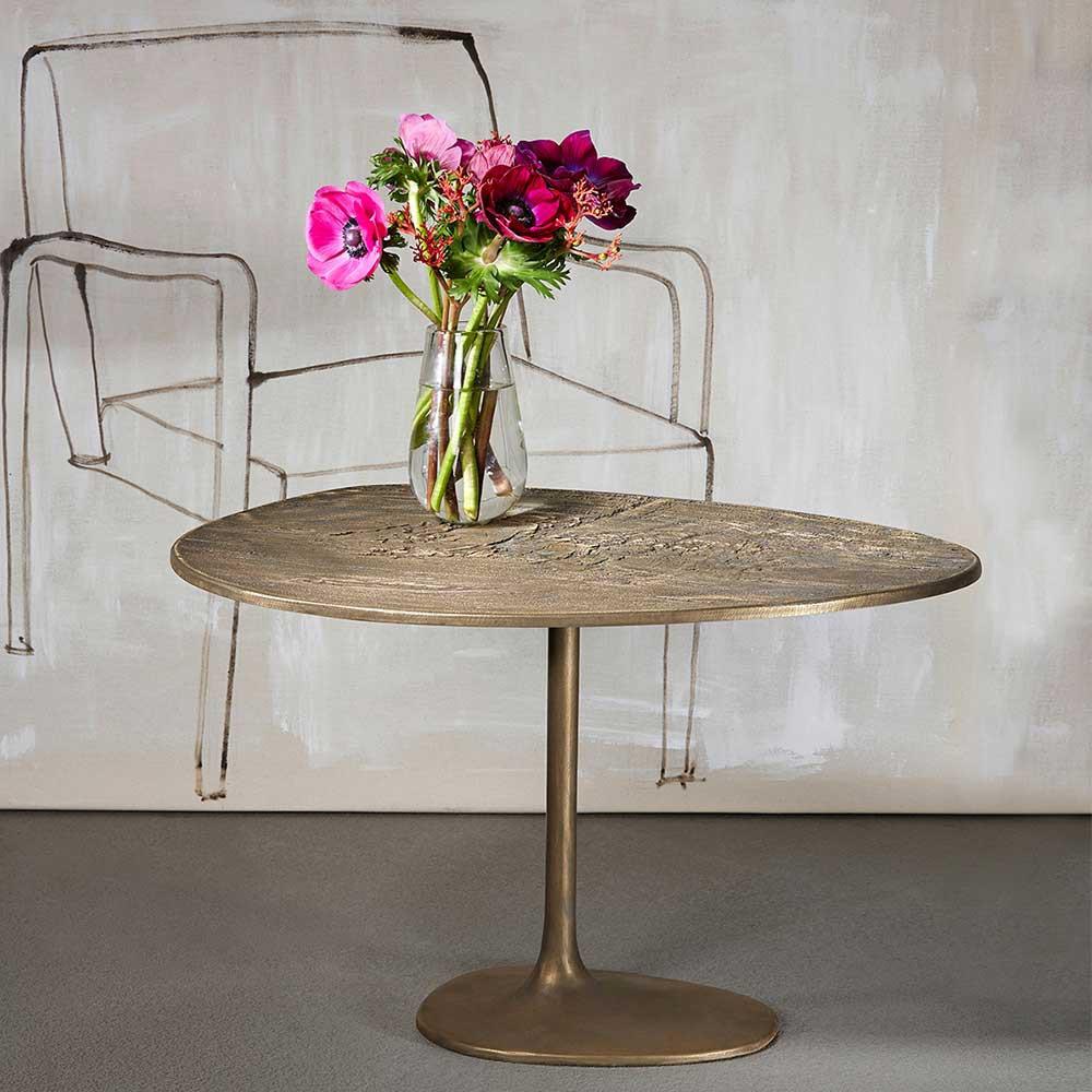 Table basse contemporaine avec un bouquet de fleur dans un vase posé sur la table, un dessin de fauteuil sur le mur
