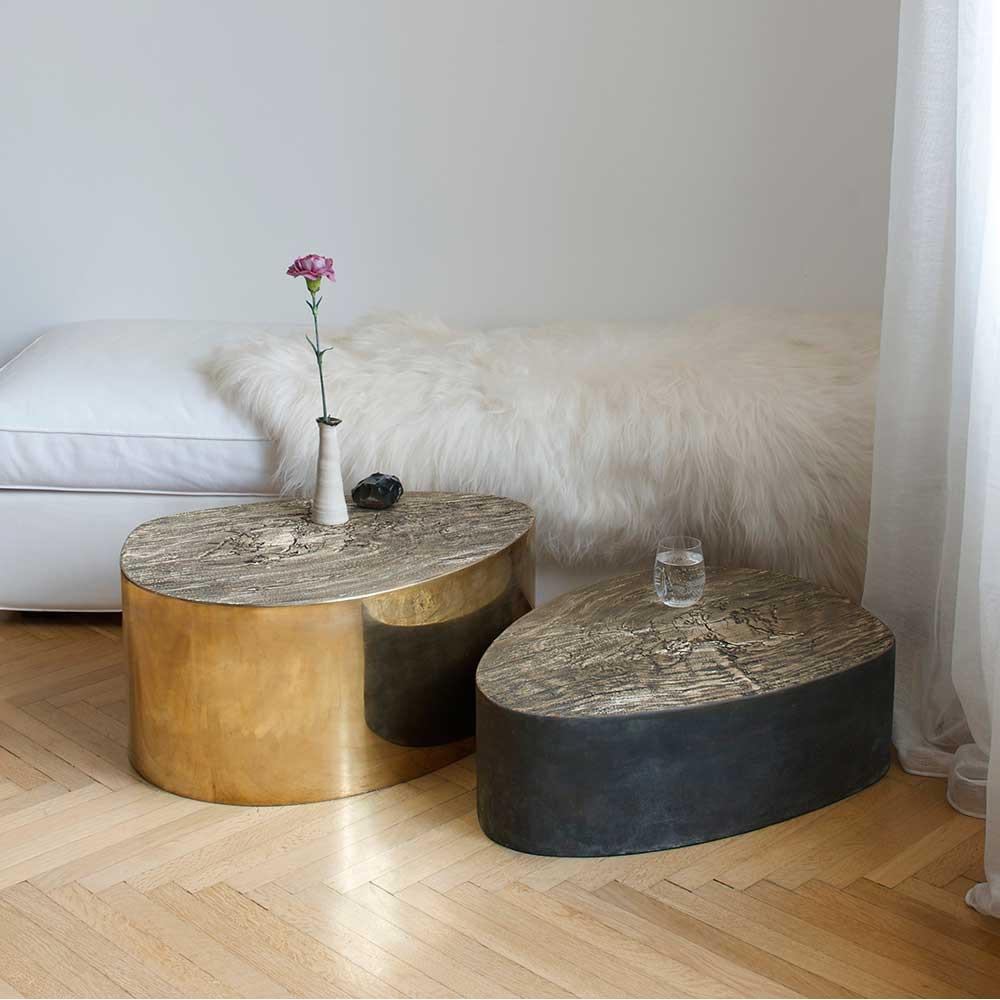 Deux tables basses en laiton, près d'une banquette/lit avec peau de mouton blanche