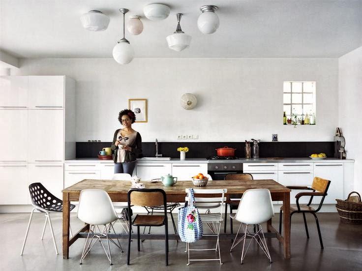Cuisine ouverte sur la salle à manger avec une grande table en bois et un ensemble de chaises dépareillées
