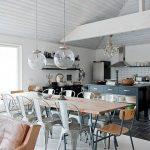 Cuisine ouverte sur la salle à manger avec table en bois et chaises Tolix
